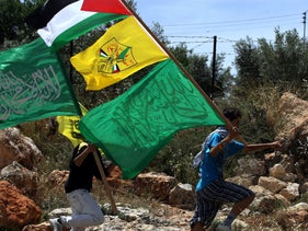 Palestinians carry the Hamas (bottom) and Fatah (C) flags to celebrate a unity deal between the two factions, in the West Bank village of Bilin, May 6, 2011.