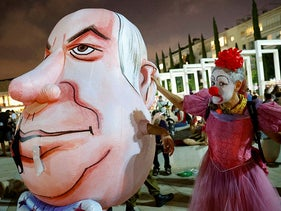 An woman wearing a clown outfit mocks a giant head costume representing Benjamin Netanyahu at a demonstration against the government, Tel Aviv, September 17, 2020.