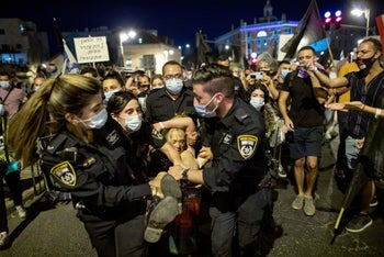 Police officers take away a protester during a demonstration asking for Netanyahu's resignation taking place in Jerusalem, despite a second coronavirus lockdown, September 20, 2020.
