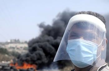 A Palestinian demonstrator stands in front of burning tires during a demonstration in Kfar Qaddum, September 4, 2020.