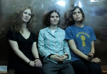 """Members of the female punk band """"Pussy Riot"""" (R-L) Nadezhda Tolokonnikova, Yekaterina Samutsevich and Maria Alyokhina sit in a glass-walled cage after a court hearing in Moscow, August 17, 2012."""