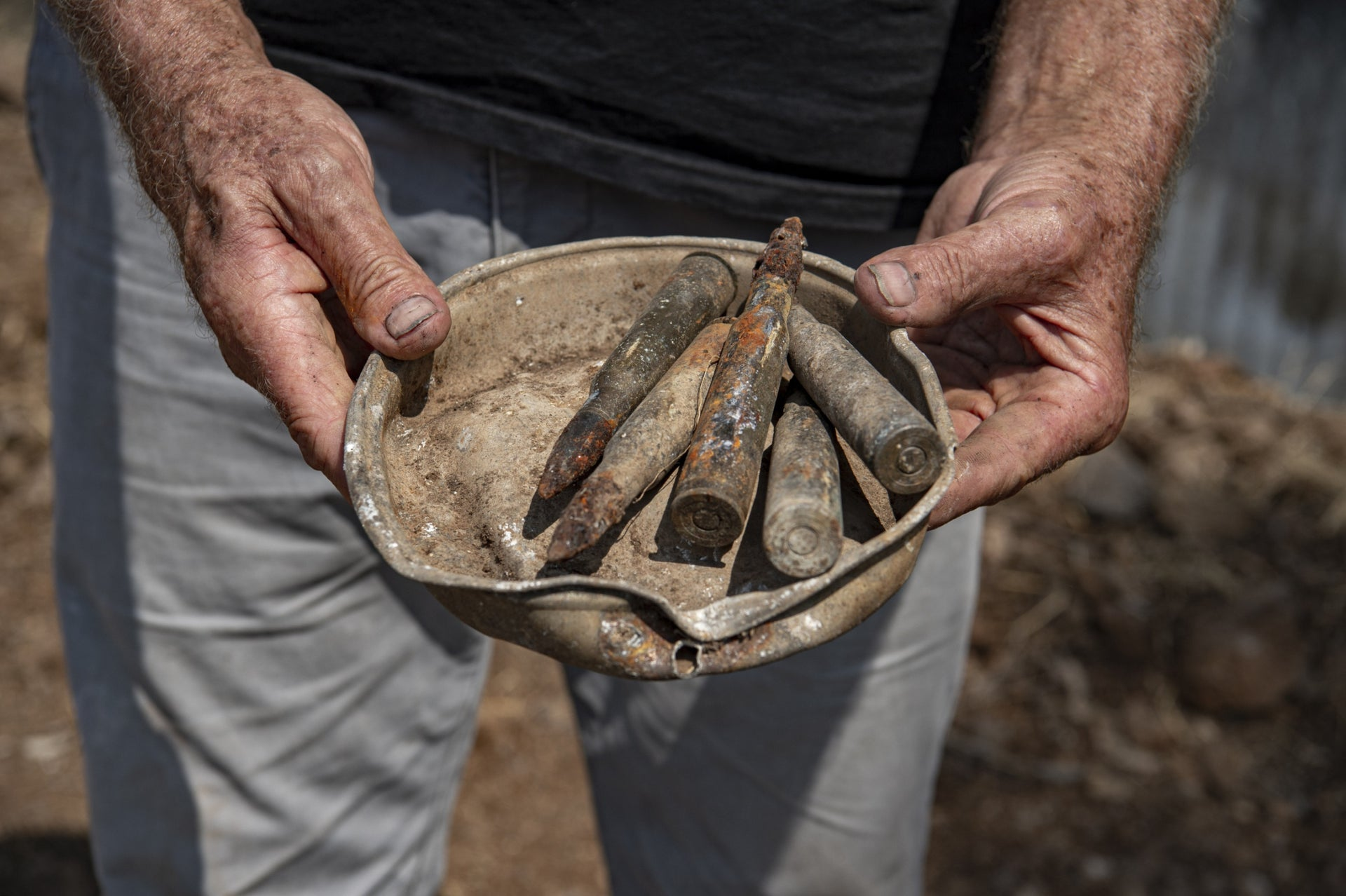 Leo Gleser holding a collection of munitions found at the site. The plan is to open a museum space at the hotel to showcase all of the findings.