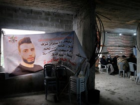 A banner with Ahmad Manasra's image at his mourning tent in the West Bank, 2019.
