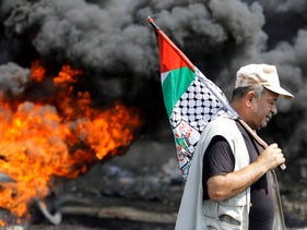 A Palestinian demonstrator passes burning tires during a protest against Jewish settlements and normalizing ties with Israel, in Kafr Qaddum, the West Bank, September 18, 2020.