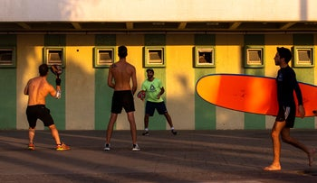 Israelis play paddleball under a closed hotel during the nationwide lockdown, Tel Aviv, September 22, 2020.