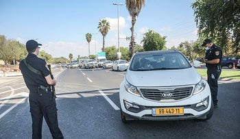Police officers stop cars at a checkpoint during Israel's second nationwide lockdown, in Tel Aviv, September 23.
