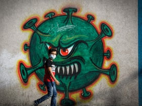 A Palestinian boy walking past street art in Gaza City depicting the coronavirus, September 22, 2020.