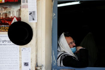 An ultra-Orthodox Jewish man looks out from the window of a synagogue in the COVID red zone of Beitar Illit, a West Bank settlement. July 8, 2020