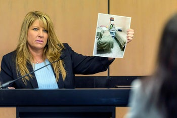 Karen Herzog, a Florida Department of Health inspector, shows a photo she took of beds in a room during her inspection of Orchids of Asia Day Spa, in court, Palm Beach, Florida, April 30, 2019.