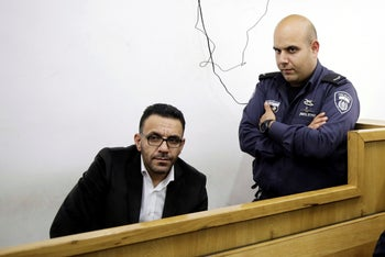 Israeli policeman stand by a Palestinian governor of Jerusalem Adnan Ghaith during a court appearance following his arrest in Jerusalem, November 29, 2018.