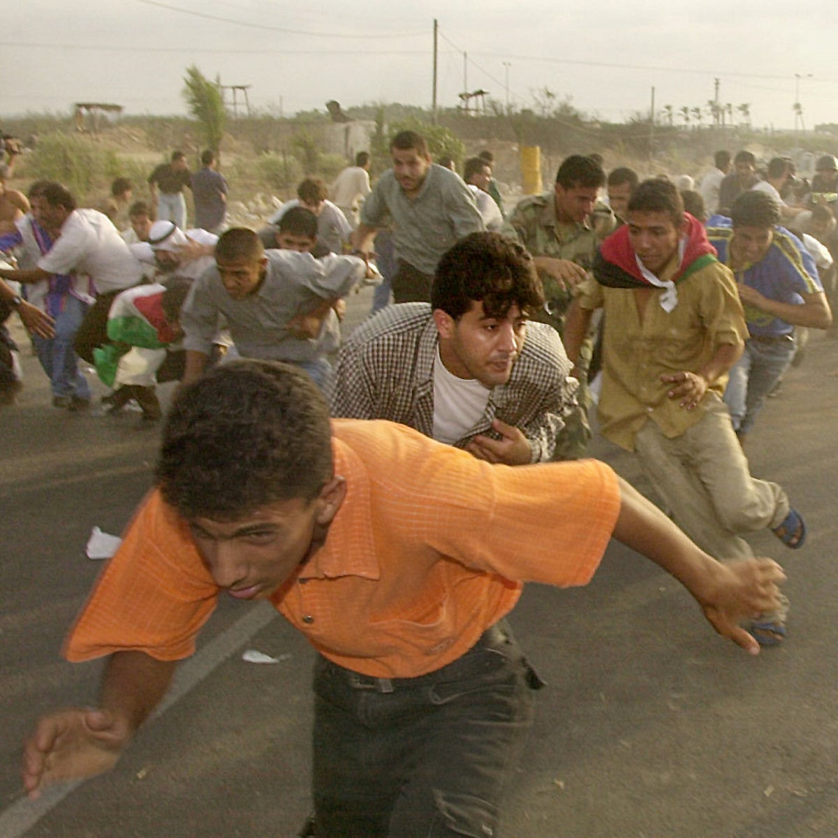 Palestinian demonstrators run for cover from heavy shooting during clashes with Israeli forces at the Netzarim Junction in the southern Gaza Strip, October 6, 2000.
