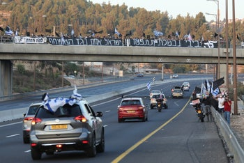 Protesters on bridges and the side of the road cheer as a convoy headed to a Jerusalem demonstration passes below them, Israel, September 26, 2020.