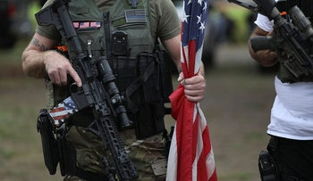 A person holds a weapon and a flag as members of the Proud Boys and other right-wing demonstrators rally on Saturday, Sept. 26, 2020, in Portland, Ore.