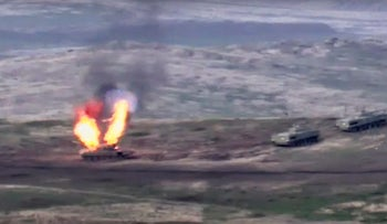 In this image taken from a footage released by Armenian Defense Ministry on Sunday, Sept. 27, 2020, Armenian forces destroy Azerbaijani tank at the contact line of the self-proclaimed Republic of Nagorno-Karabakh, Azerbaijan