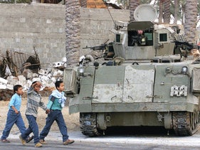 Palestinian children walking past an IDF armored vehicle protecting the settlement of Kfar Darom in southern Gaza, October 2000.