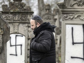 A member of the Jewish community walks among defaced gravestones at the Jewish cemetery of Herrlisheim, near Strasbourg, eastern France, Friday, Dec.14, 2018.