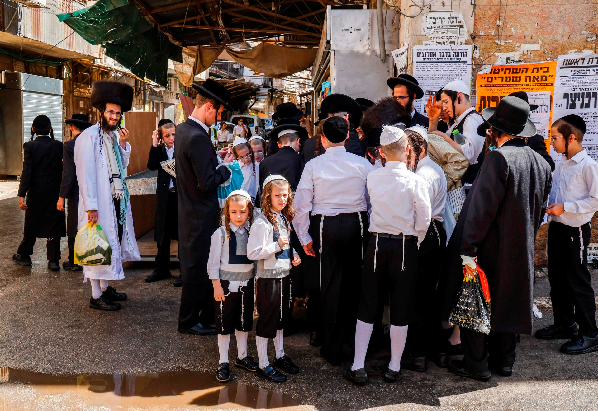 Ultra-Orthodox men and boys stand along a street corner in Mea Shearim, Jerusalem a few hours before the start of Yom Kippur, September 27, 2020.