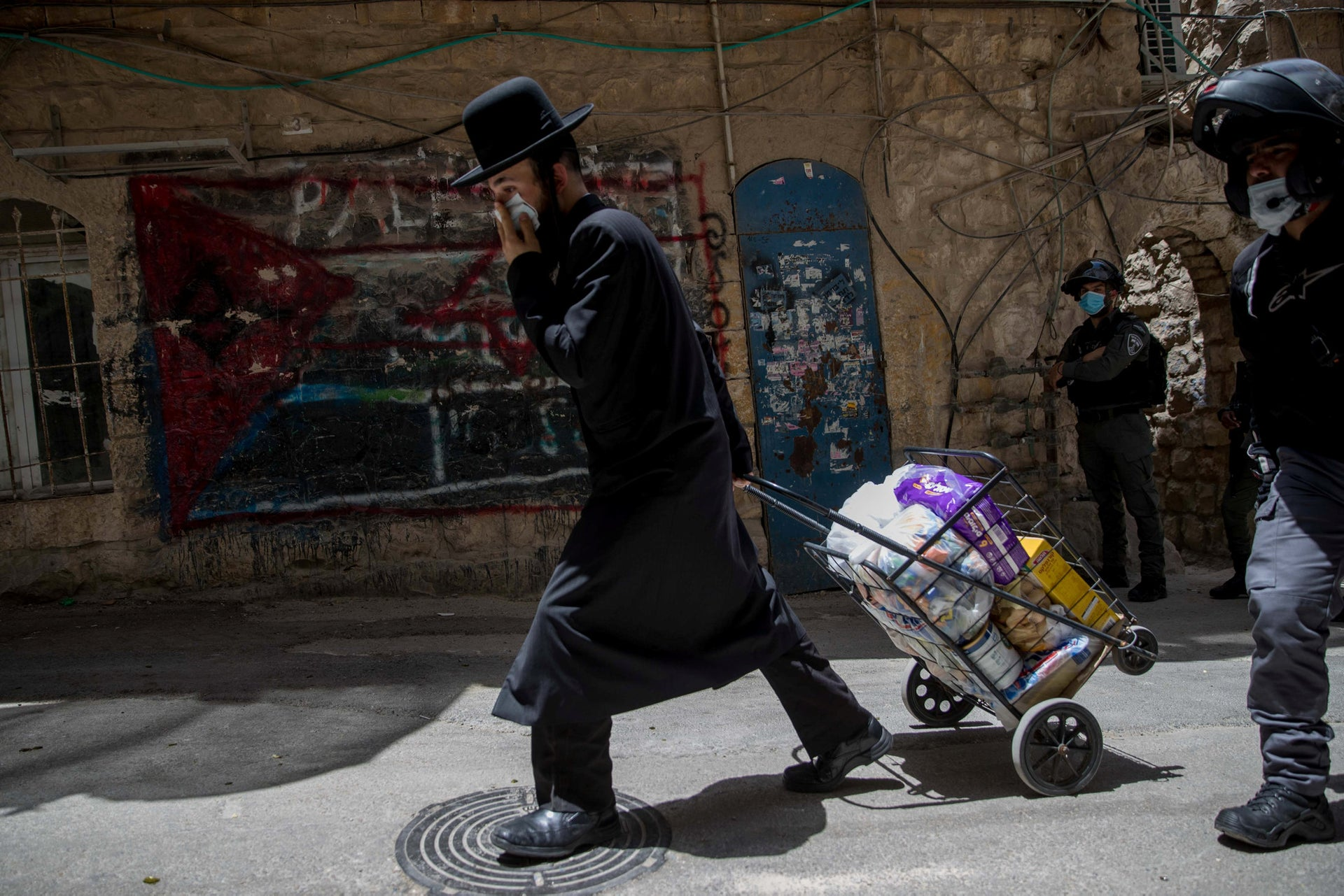 A man walks past the graffiti of a Palestinian flag in the ultra-Orthodox neighborhood of Mea Shearim, Jerusalem, June 11, 2020.