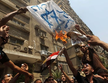 Egyptian demonstrators burn an Israeli flag during a protest outside the Israeli embassy in Cairo on August 20, 2011.