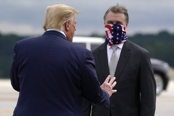 President Donald Trump greeting Sen. David Perdue, as he arrives at Dobbins Air Reserve Base for a campaign event at the Cobb Galleria Centre, September 25, 2020, Atlanta.