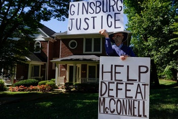 A man holding banners as protesters gather to protest outside U.S. Senate Majority Leader Mitch McConnell's home over plans to replace Supreme Court Justice Ruth Bader Ginsburg before the election, Louisville, Kentucky, September 19, 2020.