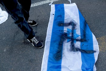 A demonstrator stands near a flag of Israel that has a swastika painted on it, as he attends a protest in Buenos Aires in 2017.