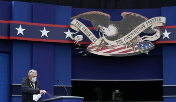 A worker sprays sanitizer on a lectern as preparations take place for the first Presidential debate in the Sheila and Eric Samson Pavilion in Cleveland, Ohio, September 28, 2020.