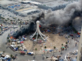Protest tents burning as Bahraini security forces, backed by forces from Saudi Arabia, storm the Pearl Roundabout. 16 March 2011