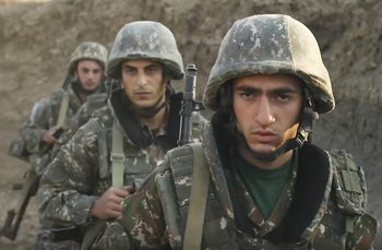 In this image taken from video released by the Armenian Defense Ministry, Armenian solders guard their position in the self-proclaimed Republic of Nagorno-Karabakh, Azerbaijan, September 30, 2020.