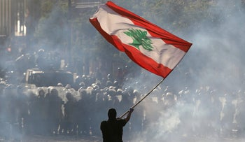 A demonstrator waves the Lebanese flag in front of riot police, Beirut, August 8, 2020