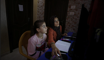 Palestinian sisters Raseel and Mariam Hussein attend their online lessons in their home, amid the coronavirus outbreak, in Gaza City, September 22, 2020.