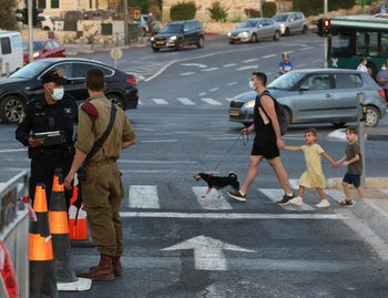 An Israeli army paratrooper and a police officer man a checkpoint to enforce coronavirus regulations in Jerusalem, September 29, 2020.
