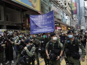 A police officer displays a warning banner on China's National Day in Causeway Bay, Hong Kong, October 1, 2020.