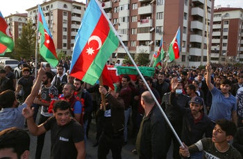 People wave Azerbaijan national flags during a funeral ceremony of a member of the Azerbaijani Armed Forces who was allegedly killed during fighting over region of Nagorno-Karabakh, September 30, 2020.