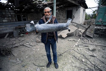 A man shows a shell fragment during fighting between Armenia and Azerbaijan over the breakaway Nagorny Karabakh region, in the disputed region's city of Martuni on October 1, 2020.