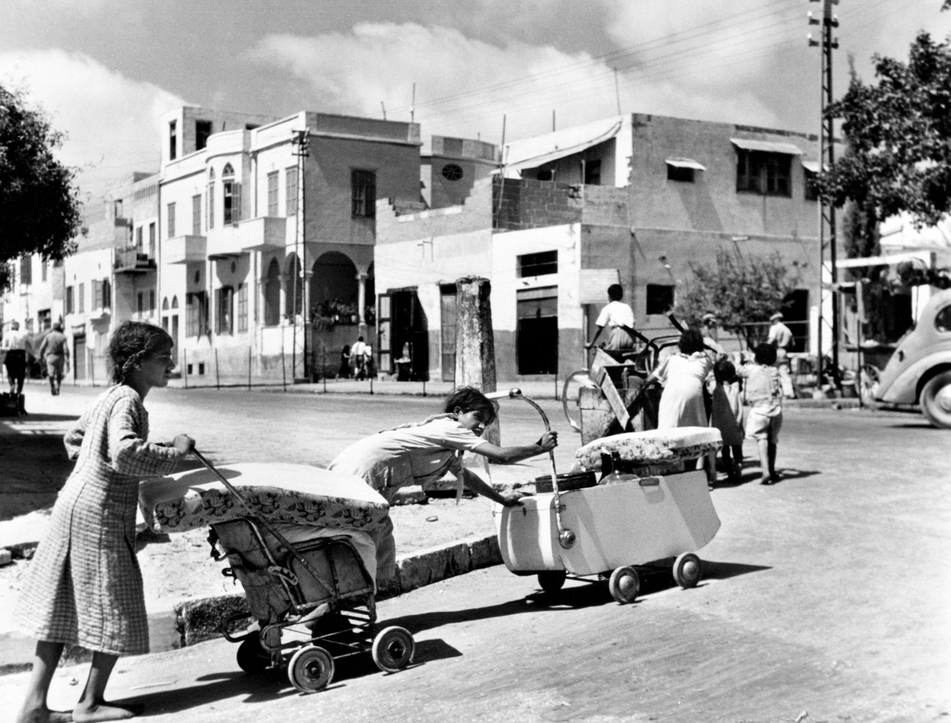 Palestinian refugee girls push their belongings in prams and carts as they flee Jaffa in the wake of the Arab-Israeli war in 1948.