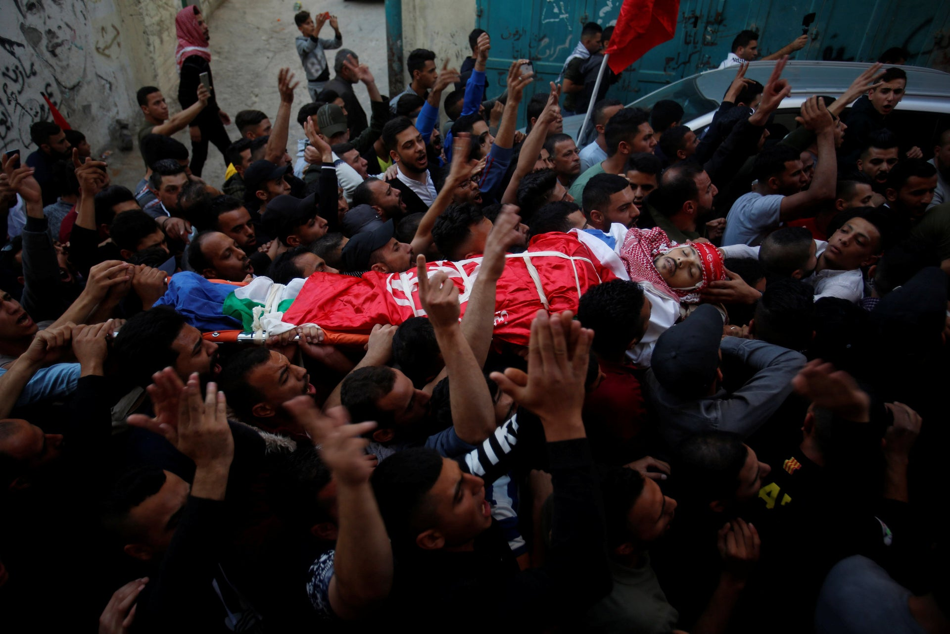 Palestinian mourners carry the body of Omar Badawi, 22, during his funeral at the al-Aroub refugee camp in the West Bank city of Hebron, Nov. 11, 2019.