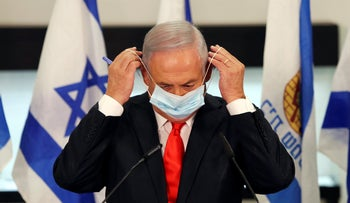 Benjamin Netanyahu adjusts his face mask during a visit to the Israeli city of Beit Shemesh, near Jerusalem, September 8, 2020.