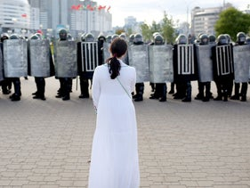 n opposition supporter stands in front of law enforcement officers blocking the street during a rally to protest against the presidential election results in Minsk on September 13, 2020.