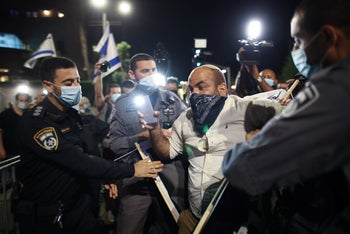 A protester clashes with police in Tel Aviv, October 3, 2020.