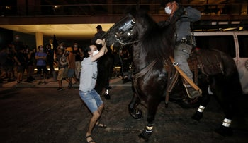 A protester confronts a mounted unit in Tel Aviv, October 3, 2020.