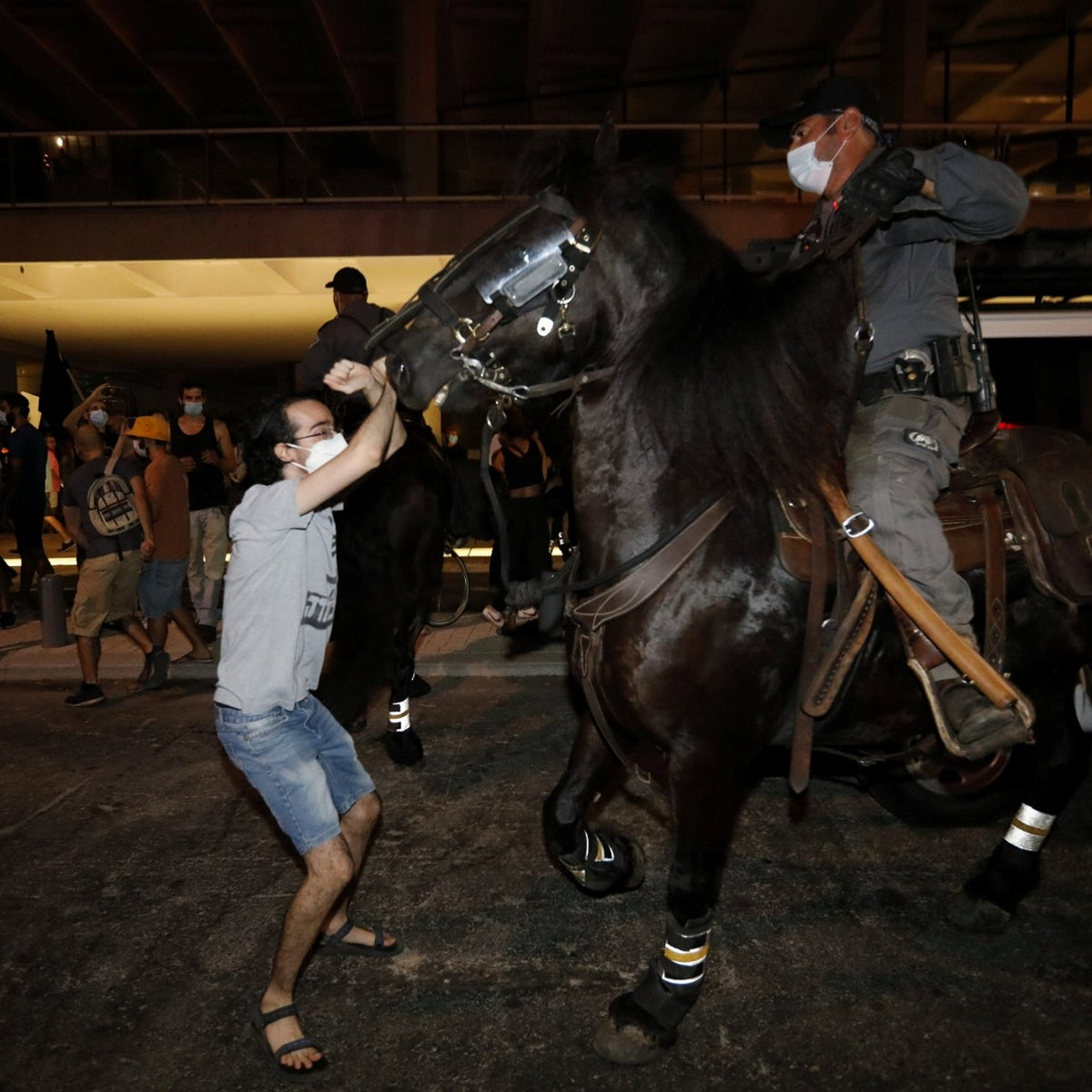 A police horse confronts a protester in Tel Aviv, October 3, 2020.