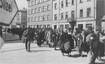 A column of captive Jews march with bundles down the main thoroughfare in Krakow during the liquidation of the Krakow Ghetto, March 1943.