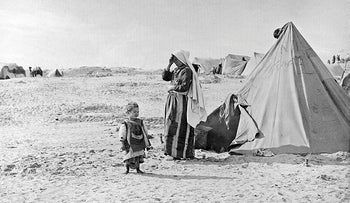 """In this 1948 photo from the UNRWA archive, Palestinian refugees stand outside their tent in Khan Younis, Gaza Strip, following what Palestinians call the """"Nakba,"""" or """"catastrophe""""-- their uprooting in the war over Israel's 1948 creation."""