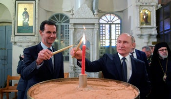 Russian and Syrian Presidents Vladimir Putin and Bashar Assad light candles while visiting an orthodox cathedral for Christmas, in Damascus, Tuesday, Jan. 7, 2020