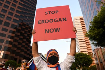 A protestor stands with members of the Armenian Youth Federation during a protest outside the Azerbaijani Consulate General in Los Angeles. Sept 30, 2020