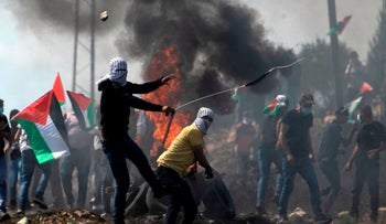 Palestinian protesters hurl stones at Israeli security forces during a weekly demonstration in the village of Kfar Qaddum on October 2, 2020