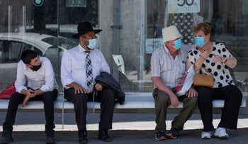 Masked people at a bus stop in Jerusalem, October 5, 2020.