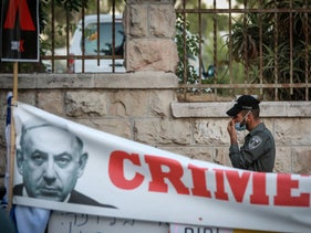 A border police officer adjusts his mask next to a sign protesting Prime Minister Benjamin Netanyahu, July 14, 2020.