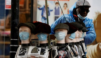 A street trader sells face masks from a stall following the outbreak of the coronavirus disease (COVID-19) in Manchester, Britain, October 5, 2020